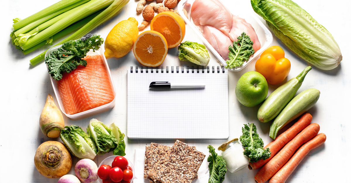 notebook and pen on a table surrounded by raw produce, fish, and chicken